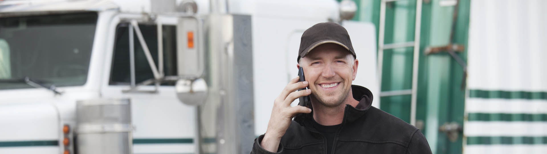 Man smiling while making a call in front of a truck